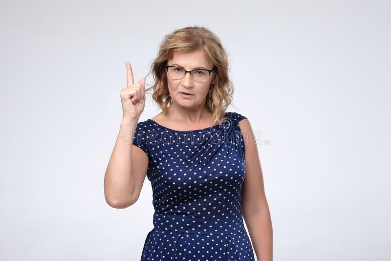 Exponeringsglas för kvinna för mogen affär som bärande pekar med fingret upp arkivfoto