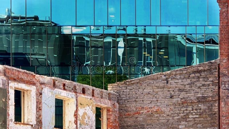 Exponeringsglas för modern nybygge för Windows reflexion blå och för gammalt tappninghus och sten av den främre förälskelse och k royaltyfria foton