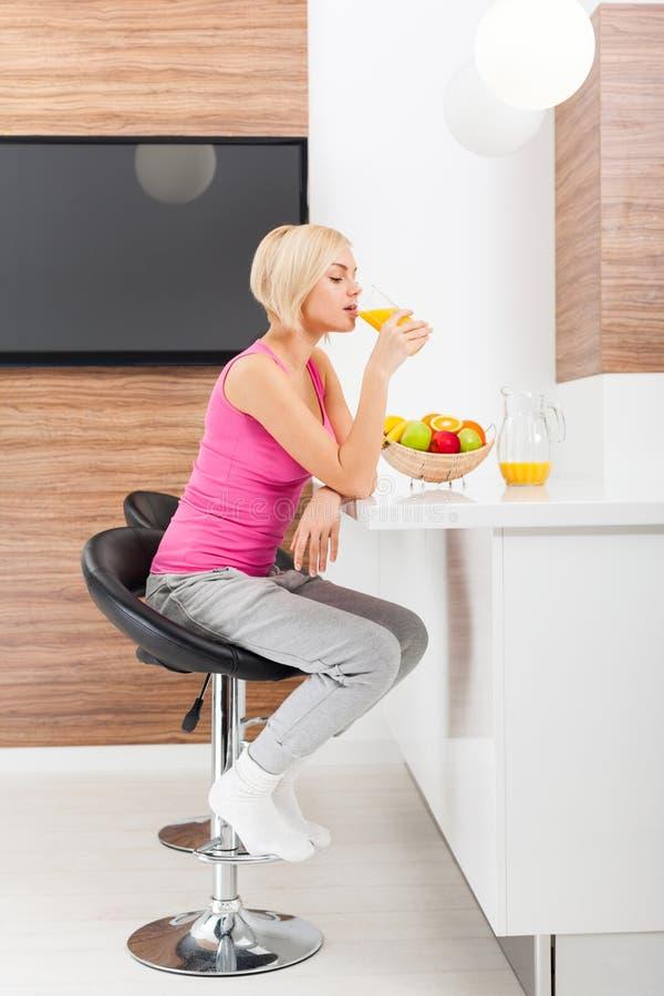 Exponeringsglas för orange fruktsaft för kvinnadrink i hennes kök arkivbilder