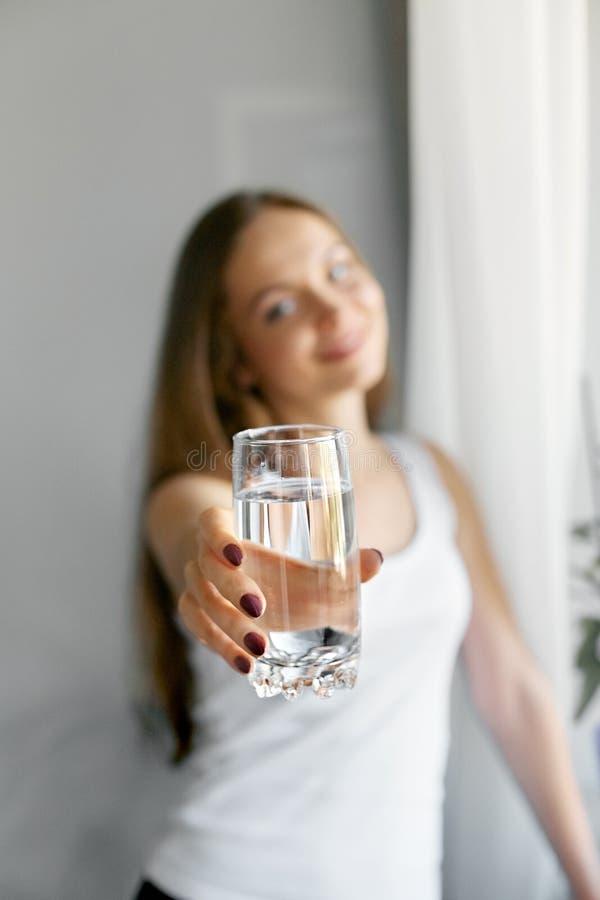 Exponeringsglas för show för ung kvinna för Closeup av vatten Stående av den lyckliga le kvinnliga modellen som rymmer genomskinl arkivbilder