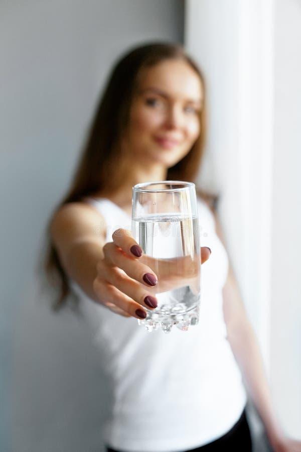 Exponeringsglas för show för ung kvinna för Closeup av vatten Stående av den lyckliga le kvinnliga modellen som rymmer genomskinl arkivfoton