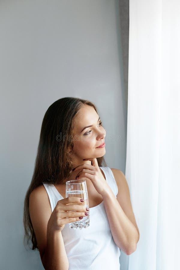 Exponeringsglas för show för ung kvinna för Closeup av vatten Stående av den lyckliga le kvinnliga modellen som rymmer genomskinl royaltyfri foto
