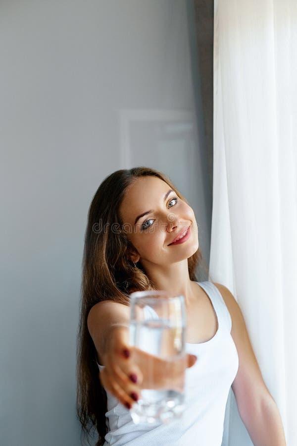 Exponeringsglas för show för ung kvinna för Closeup av vatten Stående av den lyckliga le kvinnliga modellen som rymmer genomskinl arkivbild
