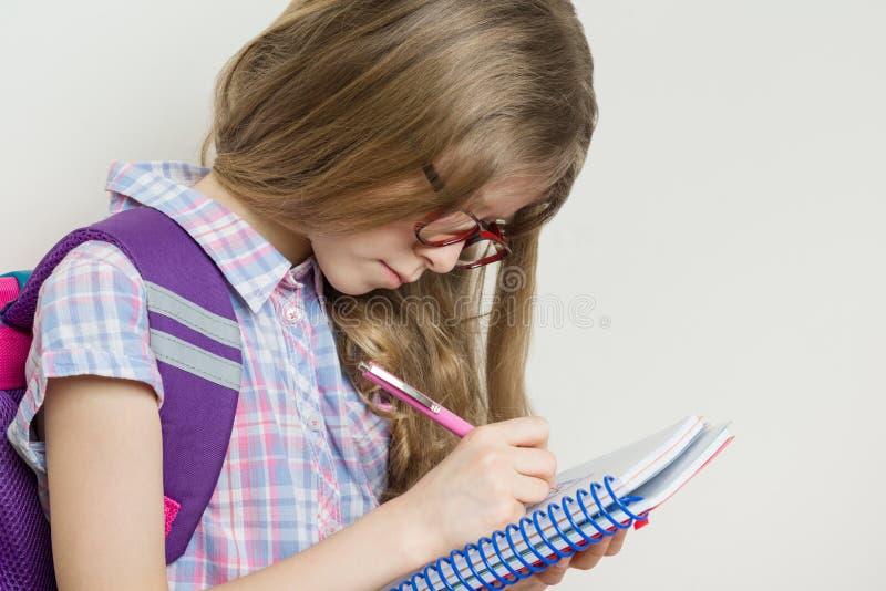 Exponeringsglas för student för flickabarngrundskola bärande med en ryggsäckhandstil i hennes anteckningsbok arkivfoton