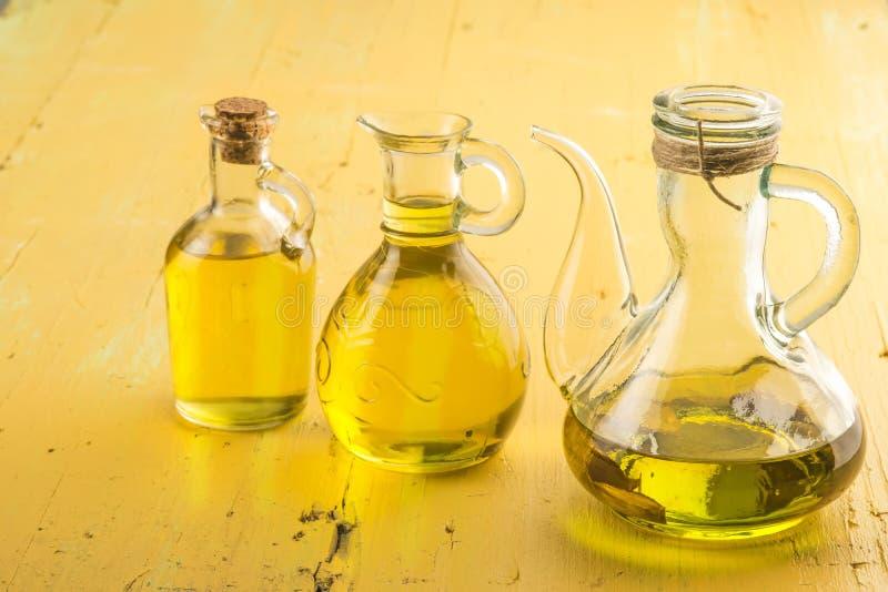 Exponeringsglas för tre oljekannor av extra olivolja royaltyfri bild