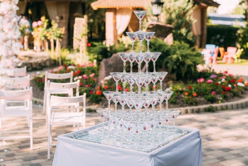 Exponeringsglas f?r alkoholdrycker Pyramid som göras av champagneexponeringsglas med körsbäret fotografering för bildbyråer