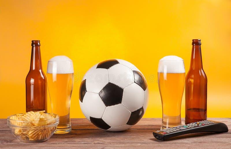 Exponeringsglas med öl och fotbollboll nära tvfjärrkontrollen royaltyfri bild