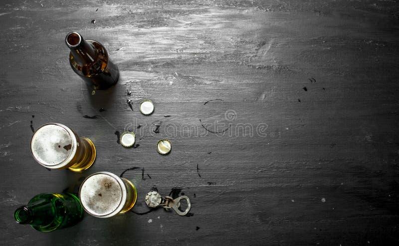 Exponeringsglas med öl, proppar och öppnaren royaltyfria bilder