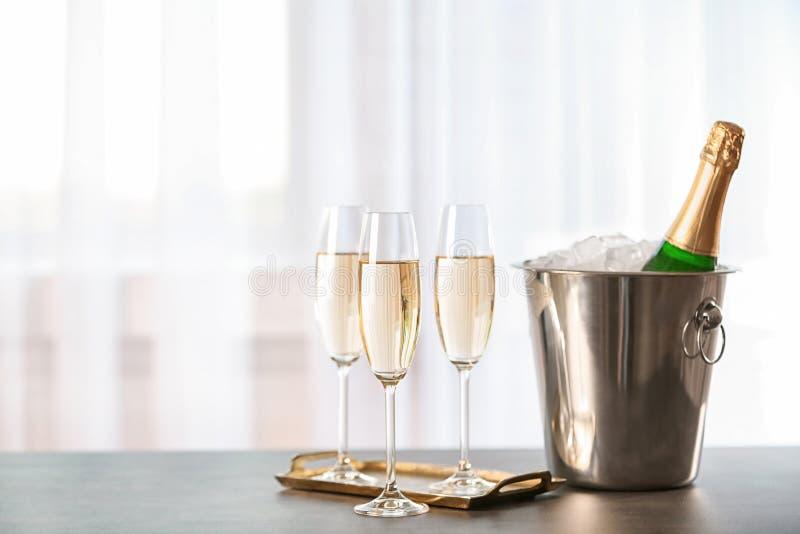 Exponeringsglas med champagne och flaskan i hink fotografering för bildbyråer