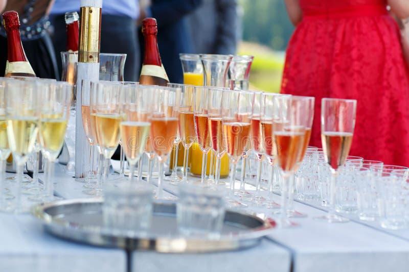 Exponeringsglas med champagne och vin på sommarbröllop arkivbild