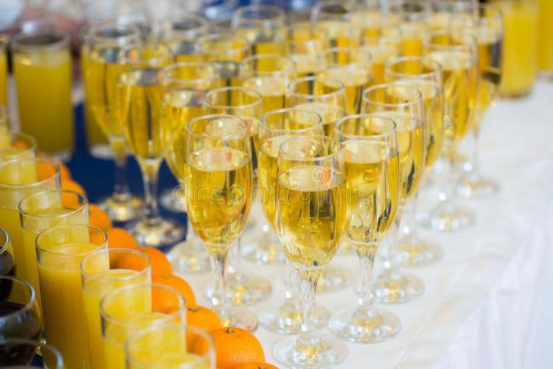 Exponeringsglas med champagne på partitabellen lott av royaltyfri foto