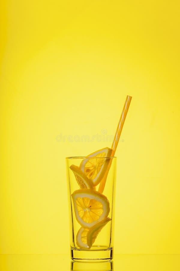 Exponeringsglas med citronen i solljus p? gul bakgrund arkivfoto
