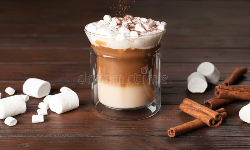 Exponeringsglas med den läckra kaffedrinken, marshmallower och kanelbruna pinnar på tabellen royaltyfri foto