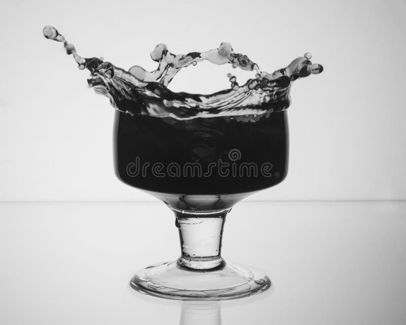 Exponeringsglas med en drink som ut plaskar arkivfoton