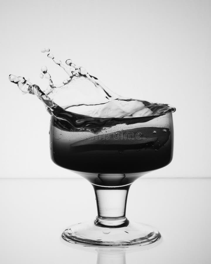 Exponeringsglas med en drink som ut plaskar royaltyfri foto