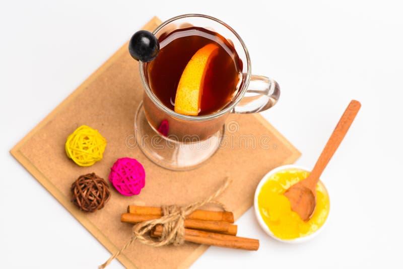Exponeringsglas med funderat vin eller varmt te med druvan, kanel och honung på vit bakgrund, bästa sikt exponeringsglas mulled w royaltyfria foton