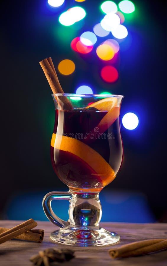 Exponeringsglas med funderat vin på mörk bakgrund med ljus fotografering för bildbyråer
