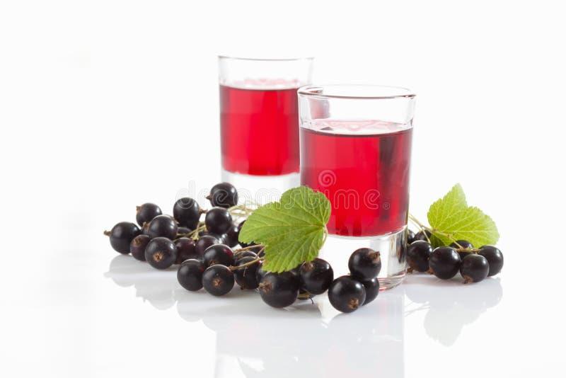 Exponeringsglas med genever, svarta vinbär royaltyfri bild