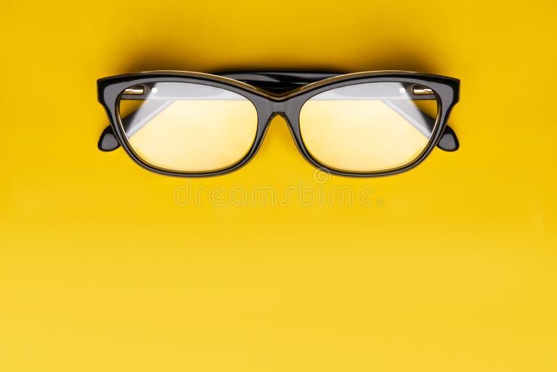 Exponeringsglas med genomskinliga linser som isoleras på gul bakgrund Fr?mre sikt med kopieringsutrymme royaltyfri bild