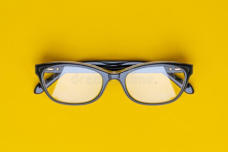 Exponeringsglas med genomskinliga linser som isoleras på gul bakgrund Fr?mre sikt med kopieringsutrymme arkivfoto