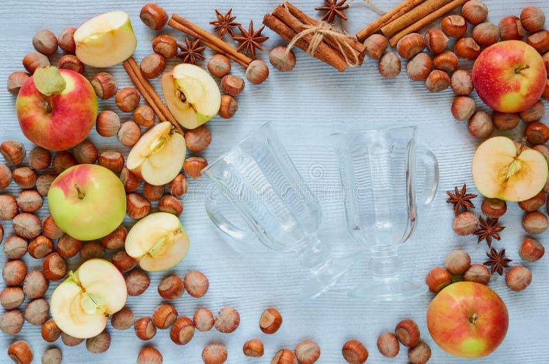 Exponeringsglas med ingredienser för funderat vin - äppleskivor, hasselnötter och jul övervintrar kryddor - kanel- och anisstjärn royaltyfria bilder