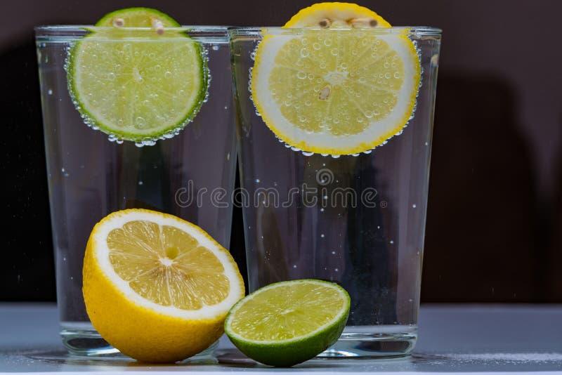 Exponeringsglas med kall mousserande mineralvatten, limefrukt och citronen arkivbild