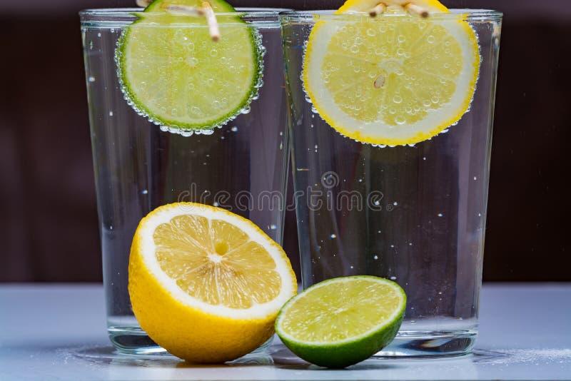 Exponeringsglas med kall mousserande mineralvatten, limefrukt och citronen royaltyfri bild