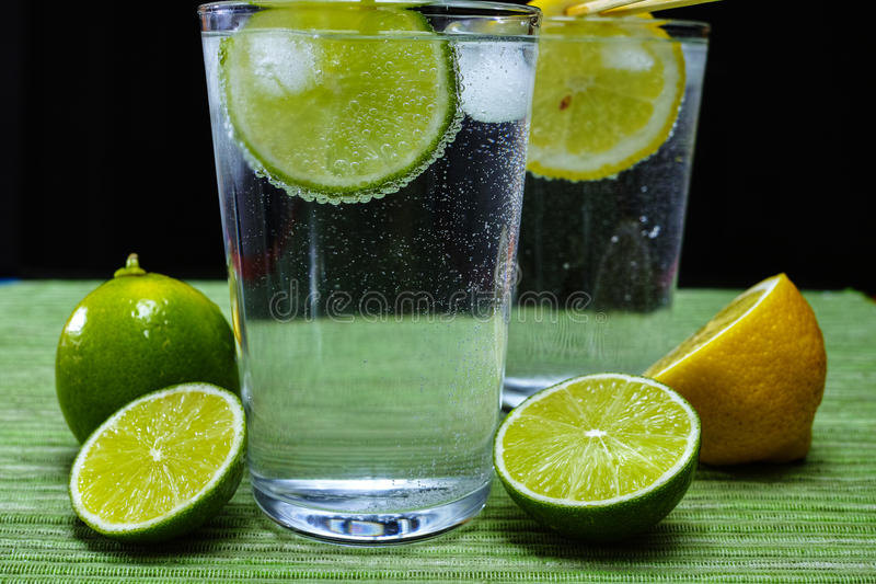 Exponeringsglas med kall mousserande mineralvatten, limefrukt och citronen royaltyfria bilder