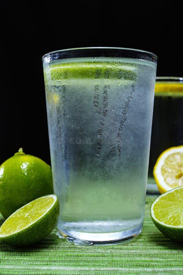 Exponeringsglas med kall mousserande mineralvatten med ny limefrukt arkivfoto