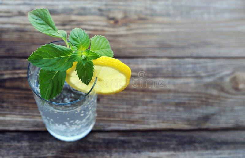 Exponeringsglas med kallt kolsyrat vatten, en skiva av en citron och nya gräsplaner av minuten royaltyfria bilder
