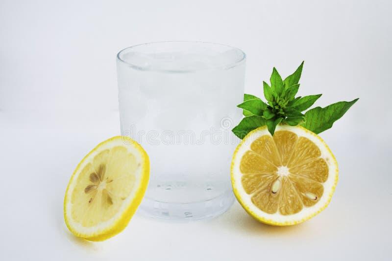 Exponeringsglas med kallt vatten, citronen och mintkaramellen Kallt vatten på en vit bakgrund arkivfoto