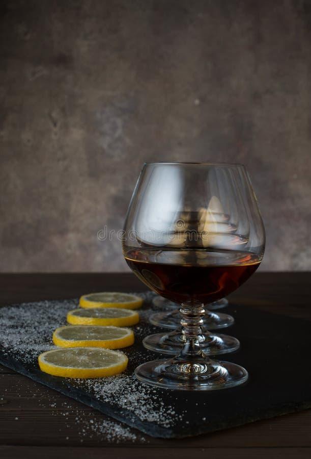 Exponeringsglas med konjak, citronskivor med socker på en trätabell i bakgrunden arkivbilder