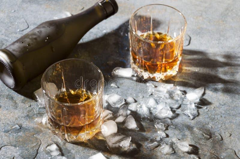 Exponeringsglas med konjak och att smälta iskuber, flaska på stångräknare royaltyfria bilder