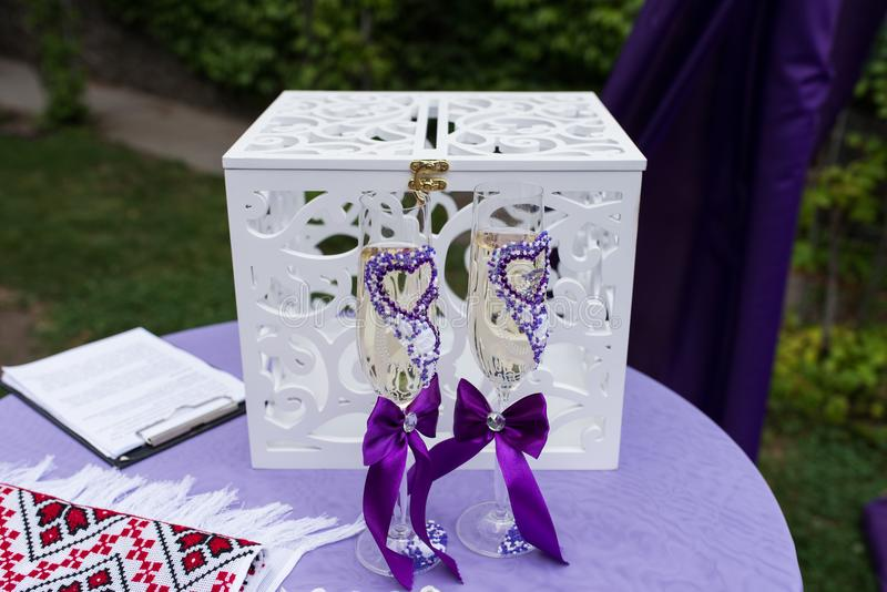 Exponeringsglas med lila hjärtor och band av bruden och brudgummen med champagne står, för de vita träaskarna i bröllop cere arkivbilder