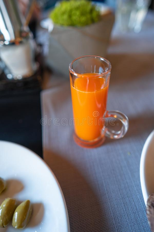 Exponeringsglas med morotfruktsaft på tabellen fotografering för bildbyråer