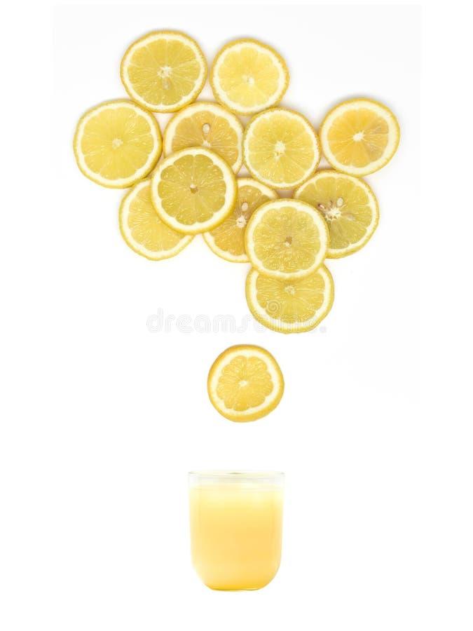 Exponeringsglas med ny citronjuice står under många citronskivor på vit bakgrund arkivbilder