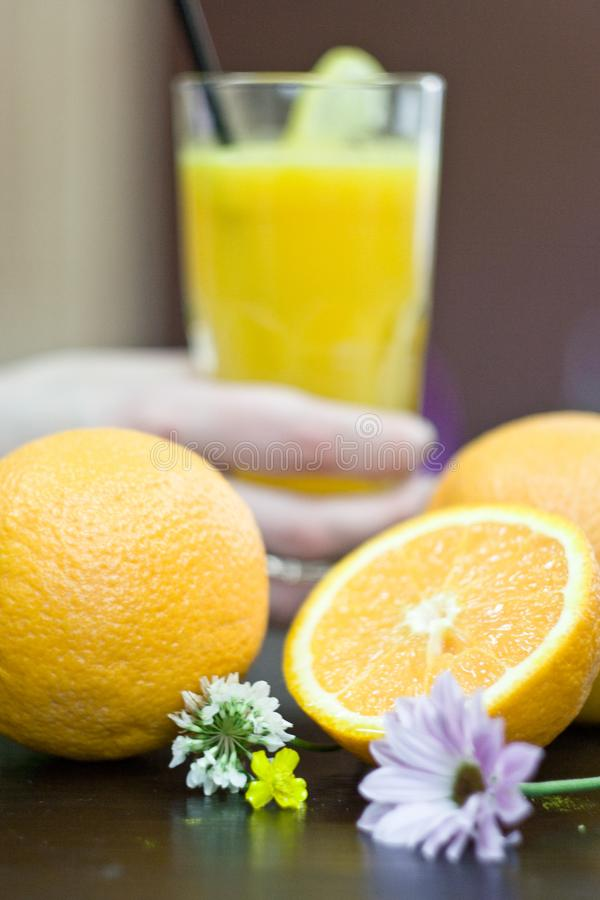 Exponeringsglas med ny orange fruktsaft och frukt på tabellen arkivbilder
