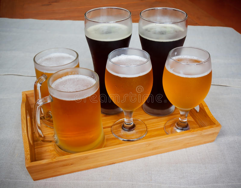 Exponeringsglas med olika slag av öl på trämagasinet arkivbild