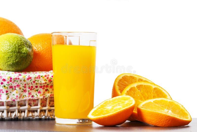 Exponeringsglas med orange fruktsaft och skivade apelsinskivor som isoleras på vit bakgrund Nytt orange nytt arkivbild
