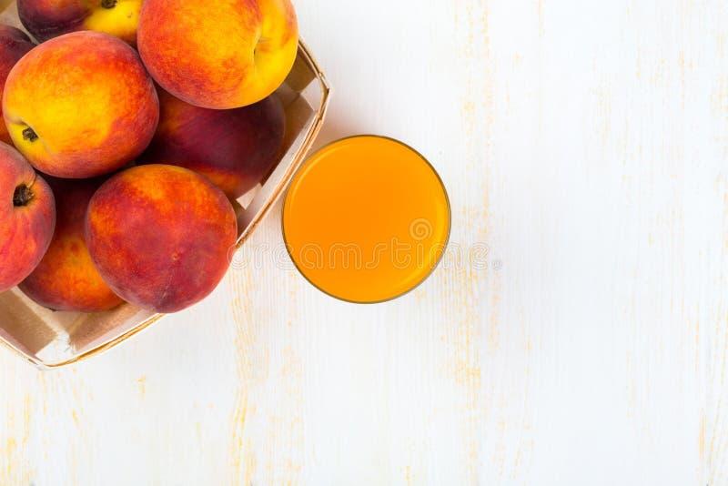 Exponeringsglas med persikafruktsaft och mogna persikor arkivbilder