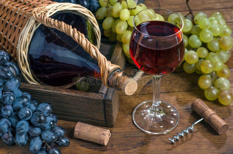 Exponeringsglas med rött vin, flaska, grupp av druvor, korkskruv på trätabellen royaltyfri bild
