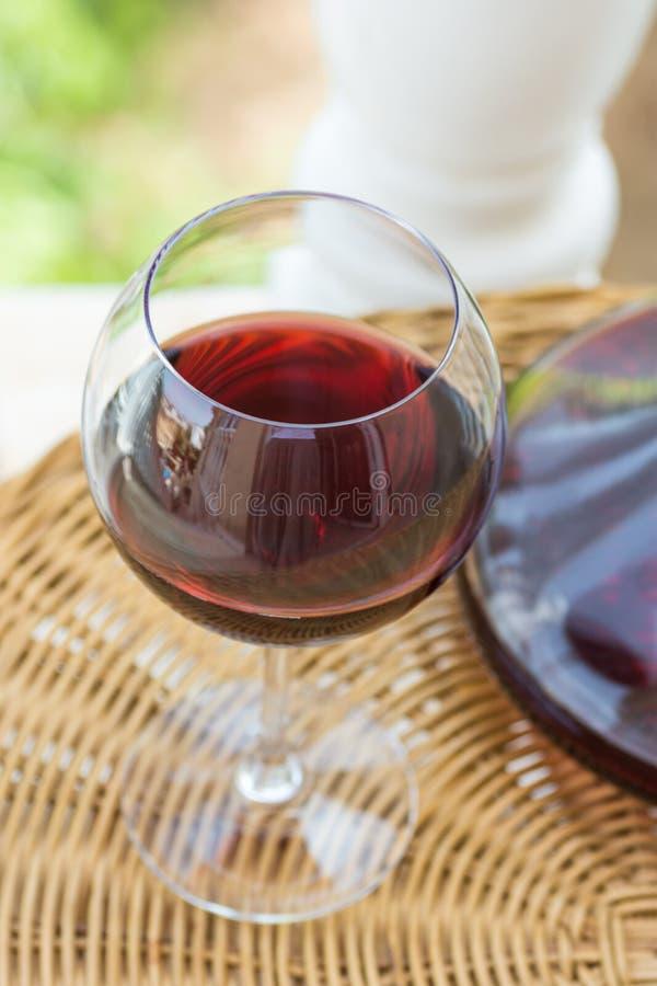 Exponeringsglas med rött vin och Crystal Decanter på den vide- tabellen i trädgårds- terrass av den lyxiga villan eller herrgårde arkivfoto