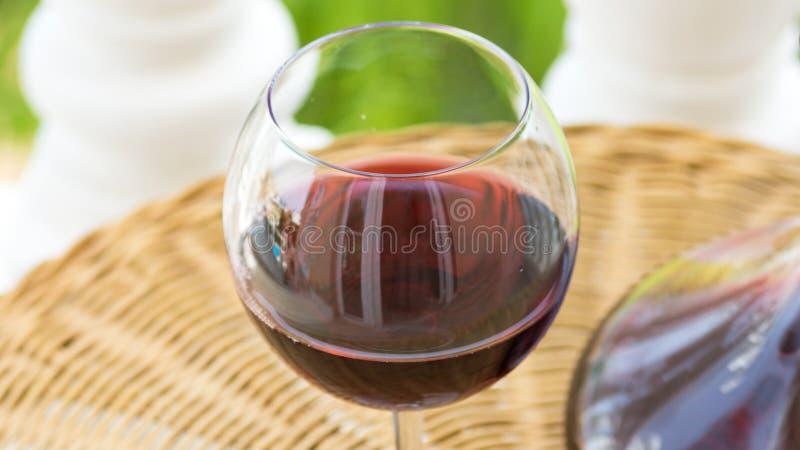 Exponeringsglas med rött vin och Crystal Decanter på den vide- tabellen i trädgårds- terrass av den lyxiga villan eller herrgårde arkivbilder