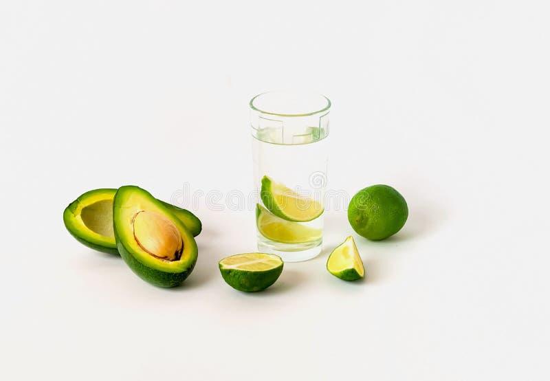 Exponeringsglas med vatten och limefrukt på vit bakgrund Detoxbegrepp Co royaltyfri fotografi