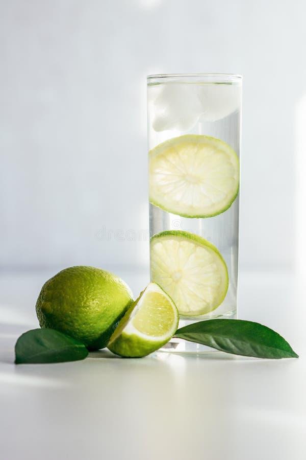 Exponeringsglas med vatten-, is- och limefruktskivor arkivfoton
