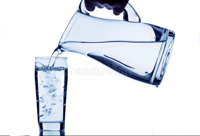 Exponeringsglas med vatten och tillbringaren arkivbild