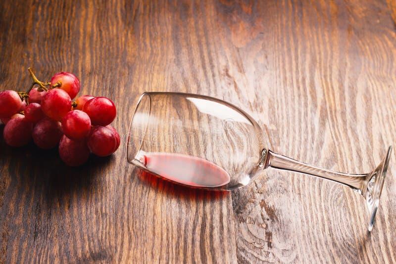 Exponeringsglas med vin bredvid gruppen av druvan arkivbild