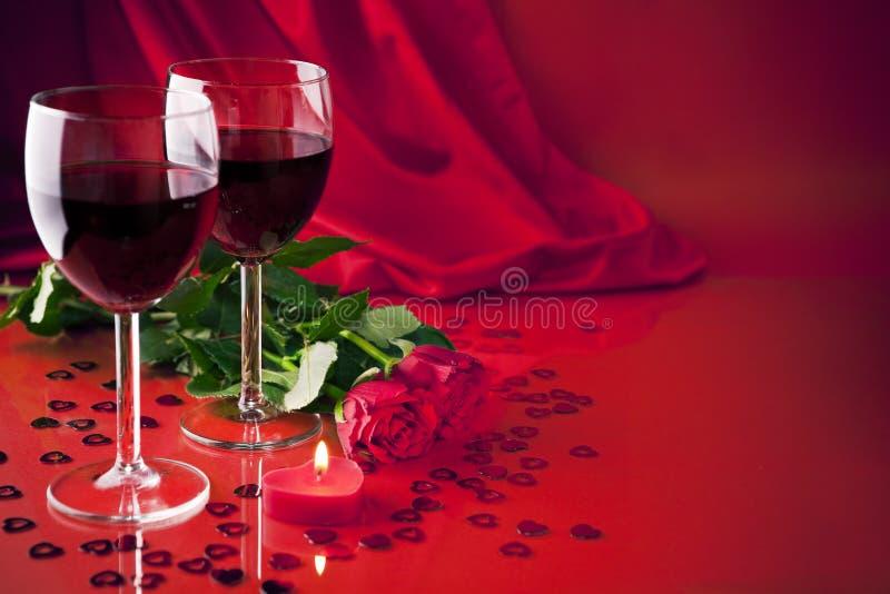 Exponeringsglas med vin, en stearinljus och rosor arkivfoton