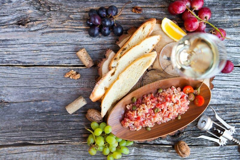 Exponeringsglas med vitt vin, druva, ost, över lantlig träbackgro arkivbilder