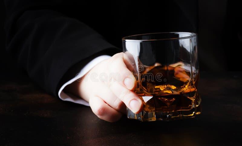 Exponeringsglas med whisky i handen, mörk bakgrund, selektiv fokus arkivbilder